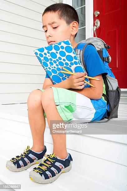 Sad Boy student waiting on front steps