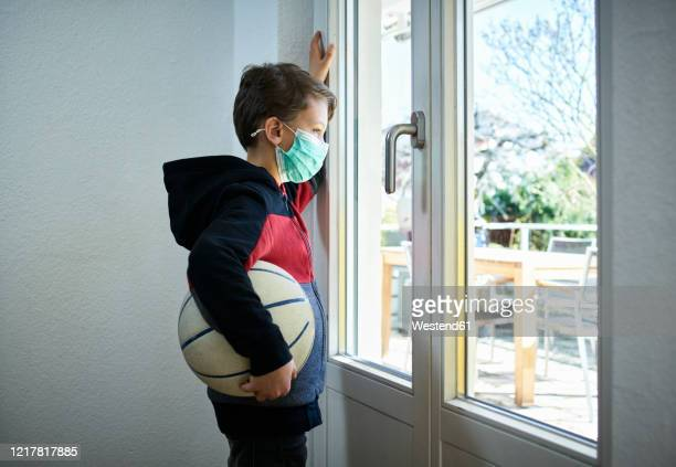 sad boy with basketball and mask looking out of window - curfew stock pictures, royalty-free photos & images