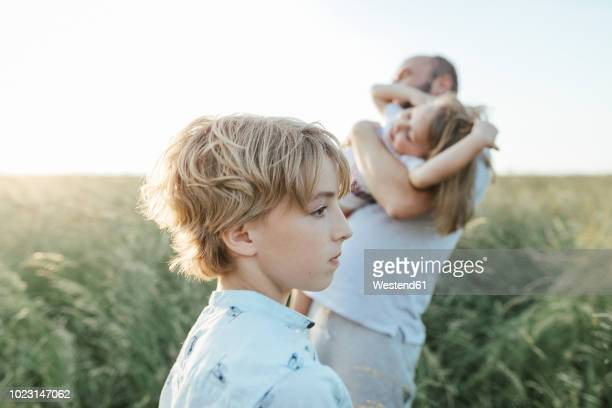 sad boy with father and sister playing together in the background - sister stock pictures, royalty-free photos & images
