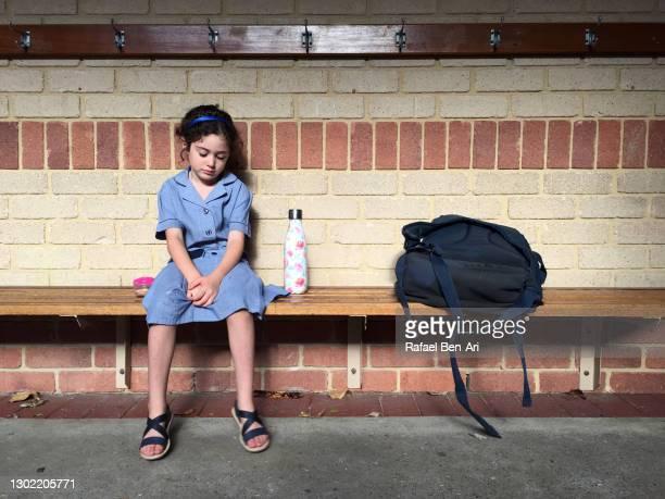 sad bullied young girl sitting alone on bench - rafael ben ari stockfoto's en -beelden