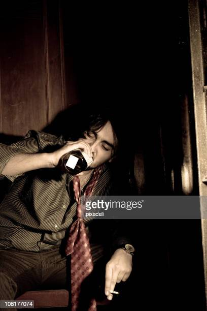 Sad Businessman Drinking From Bottle and Smoking