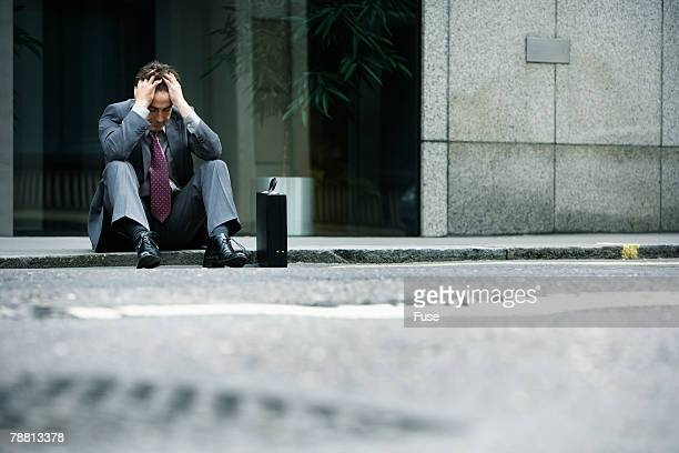 Sad Businessman Sitting on Kerb Outside Office Building