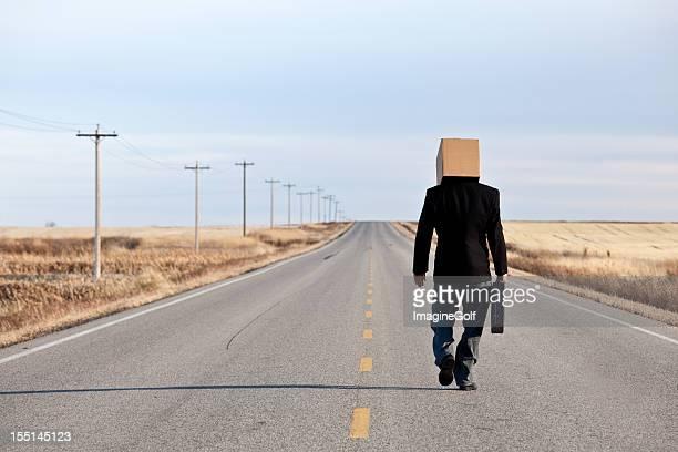 triste homme d'affaires avec boîte sur sa tête de marche le long de l'autoroute - demenagement humour photos et images de collection
