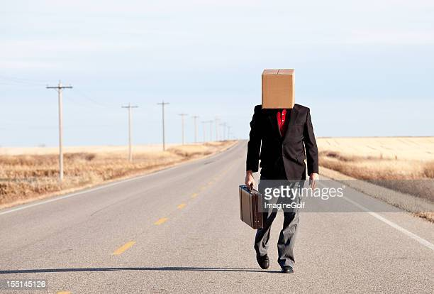 Sad Businessman with Box on His Head Walking Down Highway