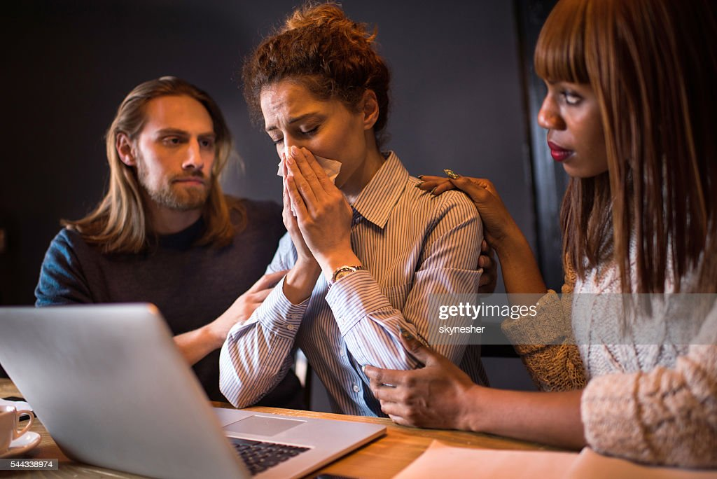 Sad businesswoman crying while her colleagues are consoling her. : Stockfoto