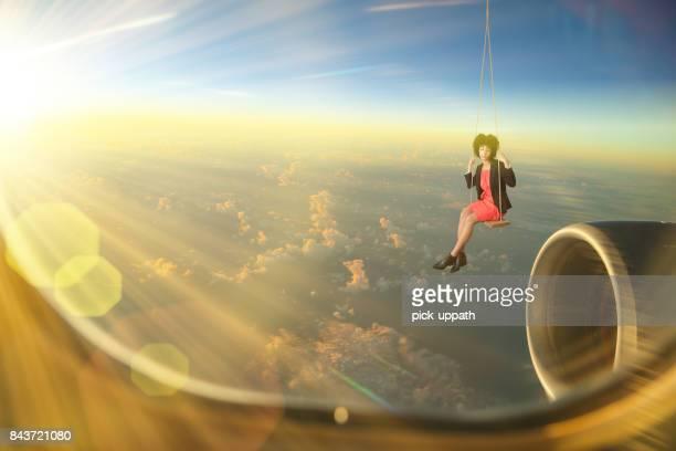 Sad businesswoman in swing over cloudscape