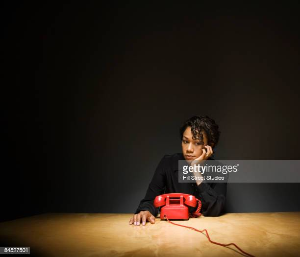 Sad businesswoman waiting for telephone to ring