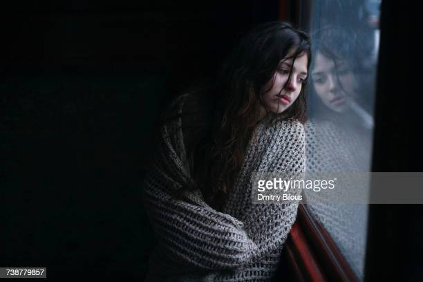 Sad Caucasian woman wrapped in scarf leaning on window