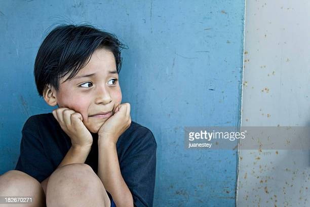A sad child leaning against a wall