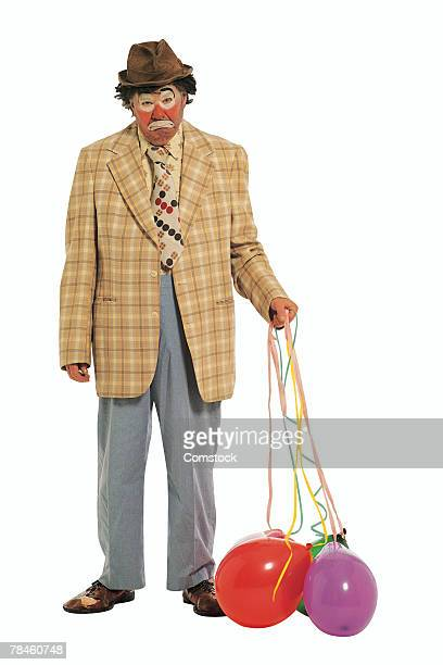 sad clown with deflated balloons - sad clown stock photos and pictures