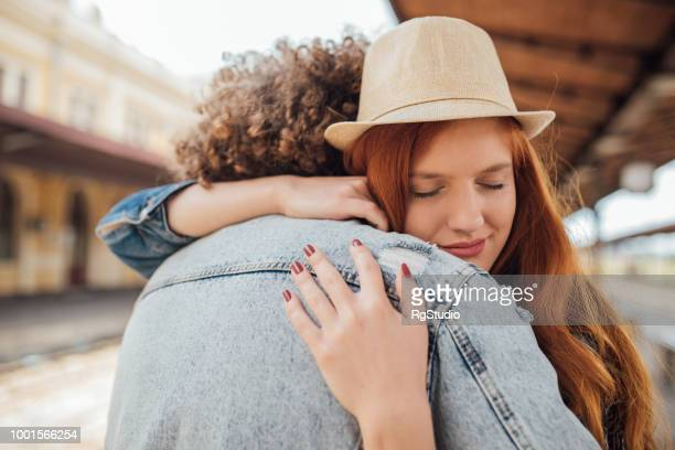 sad couple hugging while saying goodbye - long distance relationship stock pictures, royalty-free photos & images