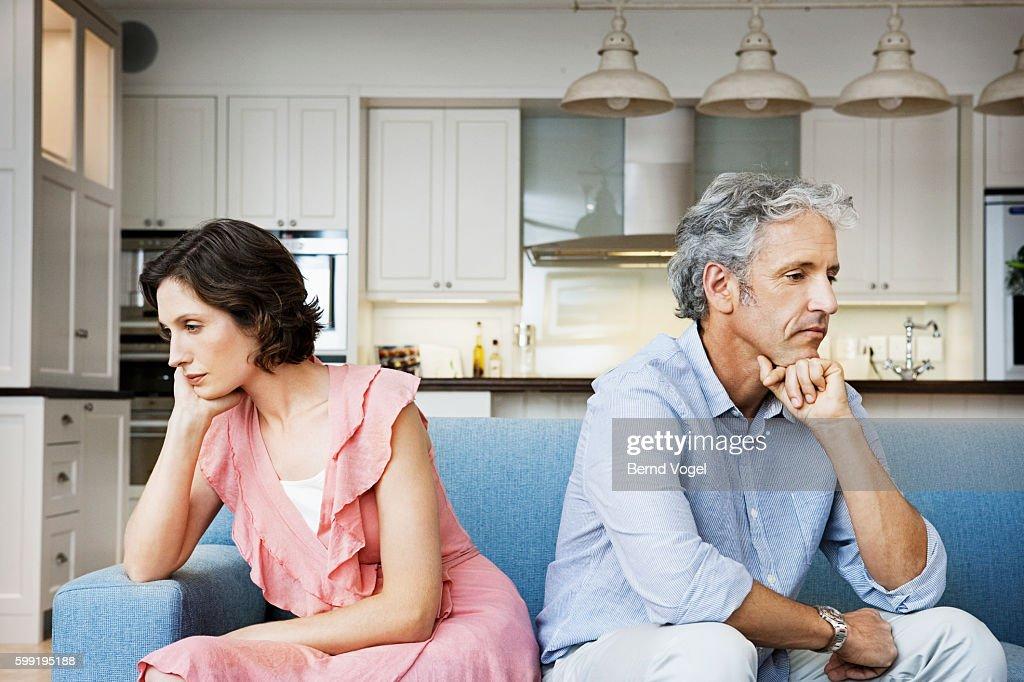 Sad couple sitting back to back : Stock Photo