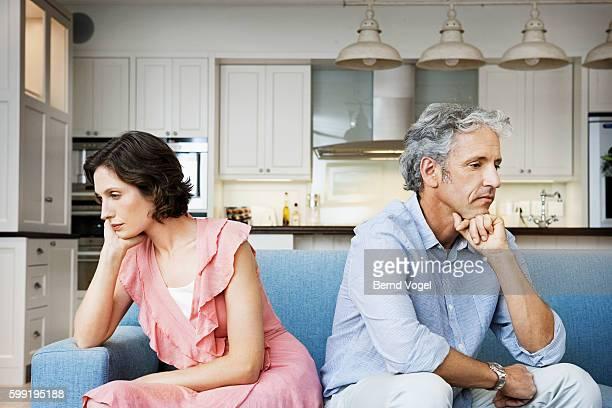 Sad couple sitting back to back