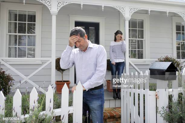 sad couple stand front their home