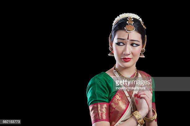 Sad dancer performing Bharatanatyam over black background