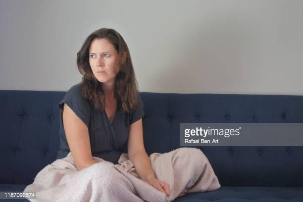 sad depressed woman sitting at home - rafael ben ari stock-fotos und bilder