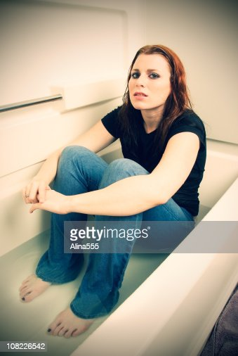 Sad Depressed Woman Sitting In A Bathtub With Water Stock