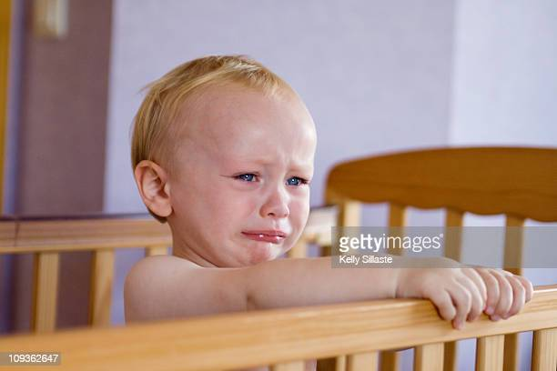 A sad faced baby boy crying in his crib