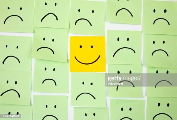 sad faces on sticky notes with one happy one - smiley face stock pictures, royalty-free photos & images