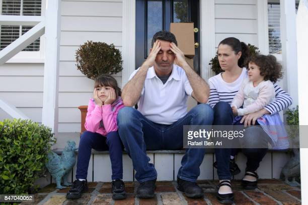 Sad family sits outside their home