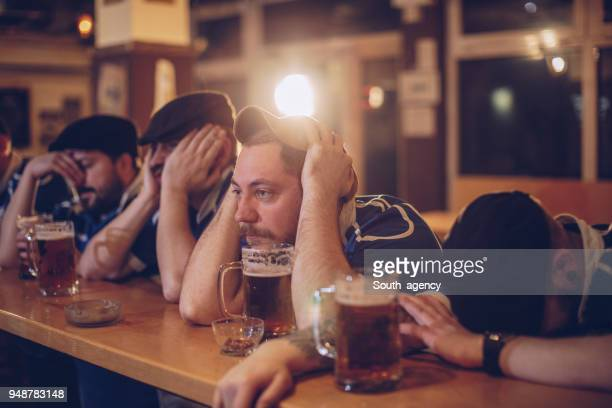 sad fans watching game - loss stock pictures, royalty-free photos & images