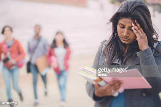 sad female college student holding her head and reading book. - winter coat stock pictures, royalty-free photos & images