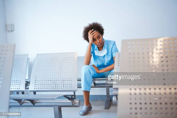 sad female nurse sitting in waiting room - outpatient care stock pictures, royalty-free photos & images