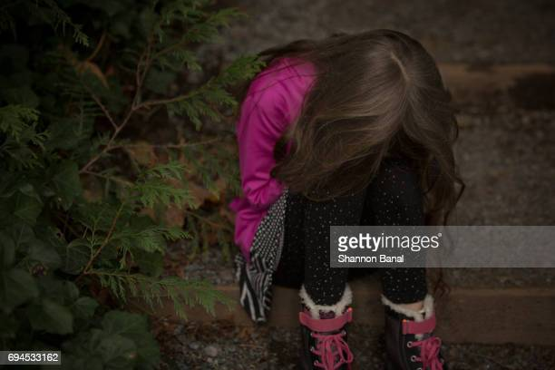 Sad Girl Hides Face in Lap in Forest