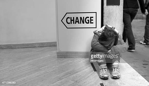 Sad girl huddled by sign saying change