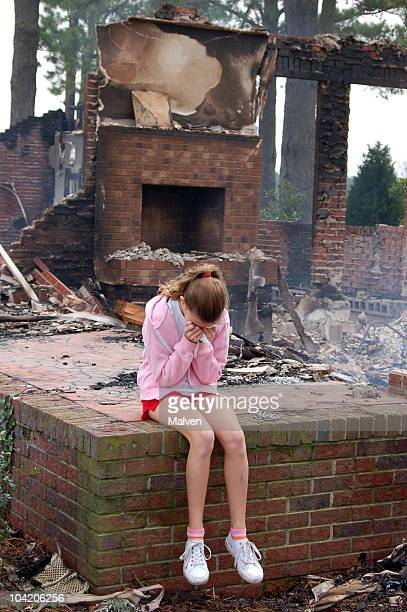 Sad girl sitting in a ruined place on a brick stage