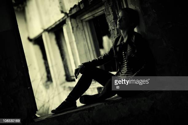 Sad girl sitting in the dark ruins and smokes