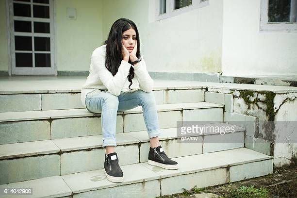 sad girl thinking and sitting on steps, holding her head. - girls stock pictures, royalty-free photos & images