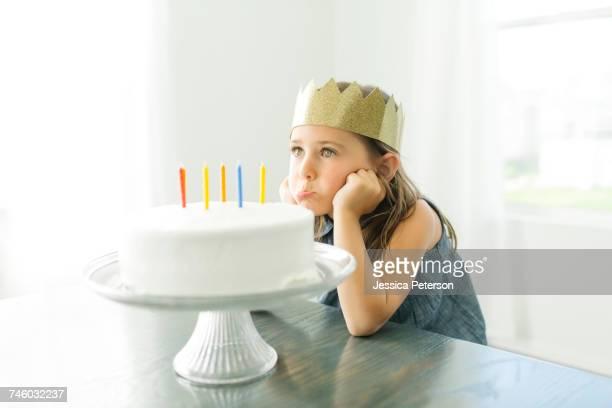 Sad girl (6-7) with birthday cake