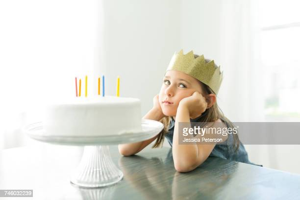 sad girl (6-7) with birthday cake - happybirthdaycrown stock pictures, royalty-free photos & images