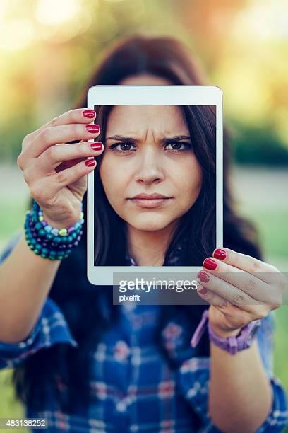 Sad girl with digital tablet making selfie