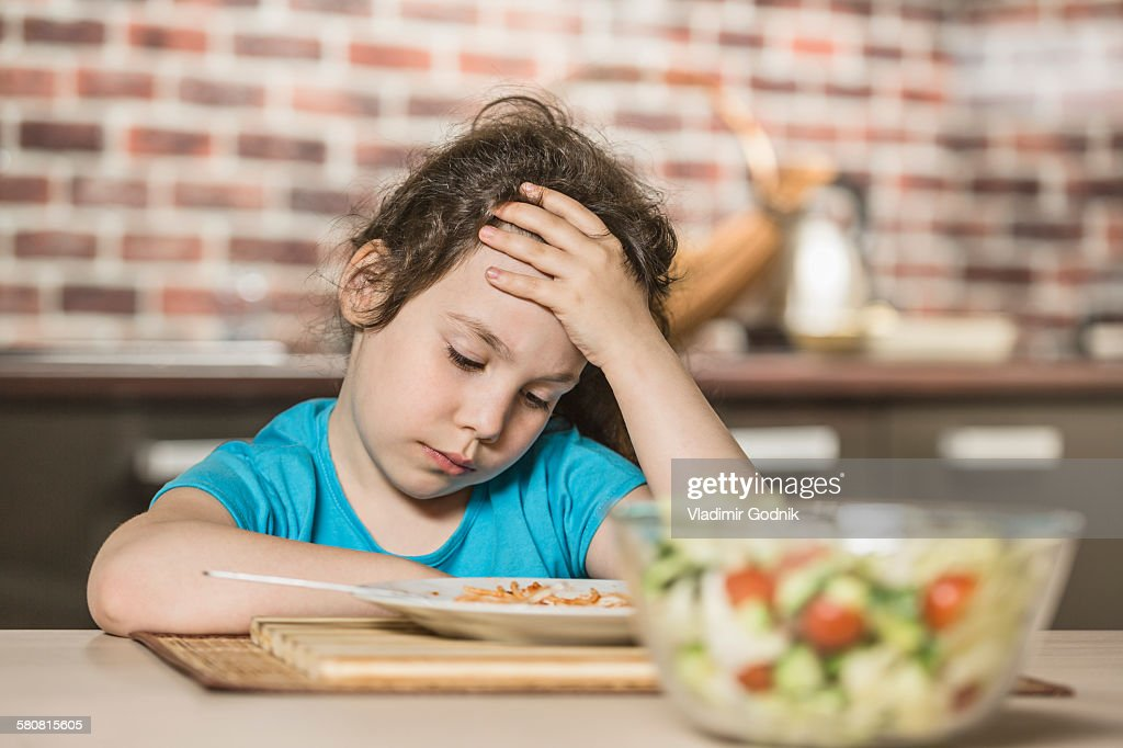 Sad girl with head in hand while having breakfast at table : Stock Photo