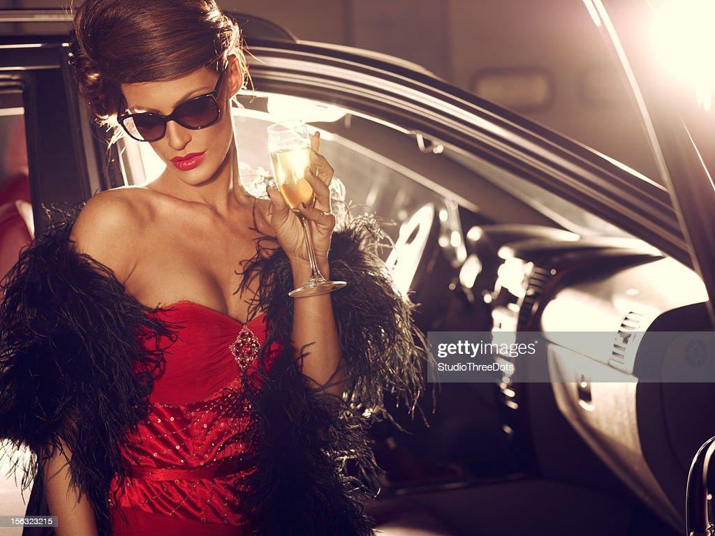 Triste femme glamour debout près de voiture de luxe avec du Champagne
