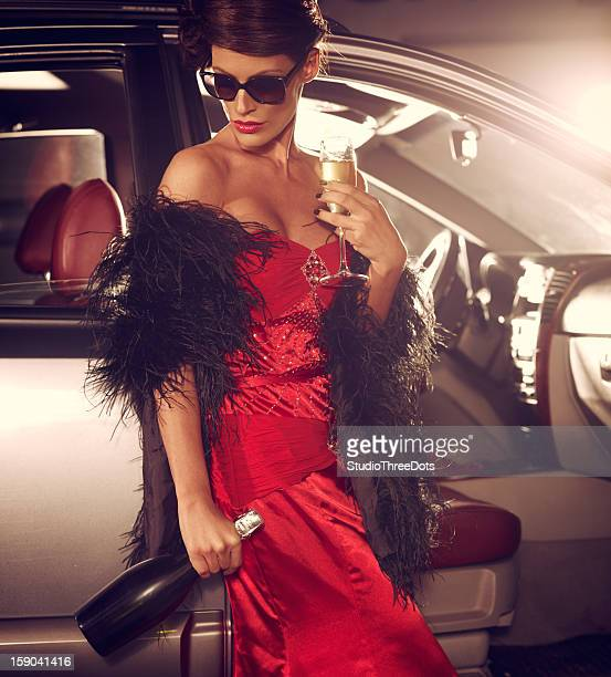 sad glamorous woman standing next to luxury car with champagne - millionnaire stock photos and pictures
