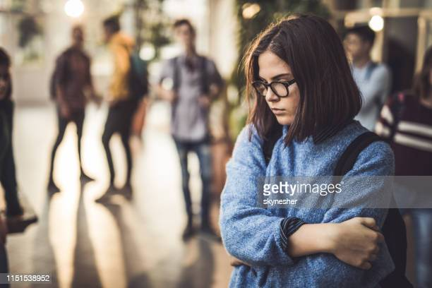 sad high school student feeling lonely in a hallway. - adolescente imagens e fotografias de stock