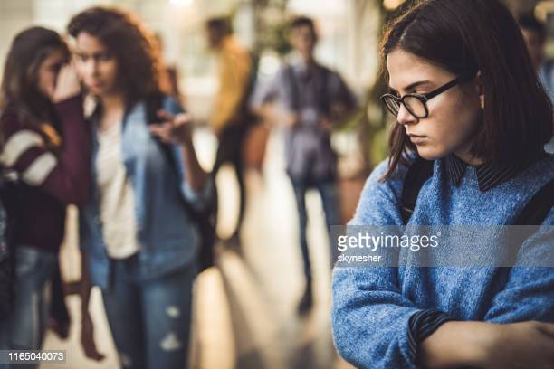 sad high school student feeling lonely in a hallway. - bullying stock pictures, royalty-free photos & images