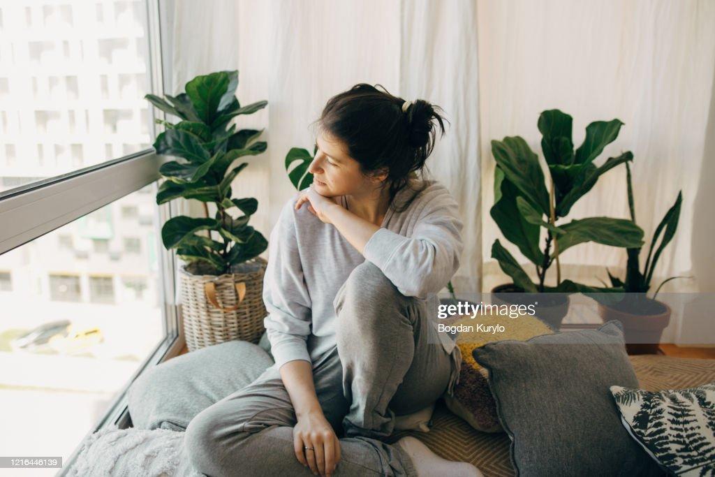Droevige hipstermeisjeszitting thuis tijdens quarantaine en het bekijken van venster. Blijf thuis, blijf veilig. Isolatie thuis om virusepidemie te voorkomen. Jonge vrouw die in moderne ruimte ontspant : Stockfoto