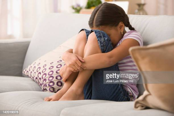 sad hispanic girl sitting on sofa - vulnerability stock pictures, royalty-free photos & images
