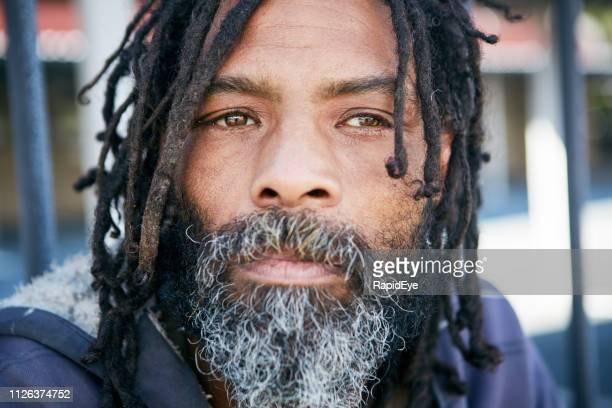 sad homeless person with rastafarian dreadlocks - homelessness stock pictures, royalty-free photos & images