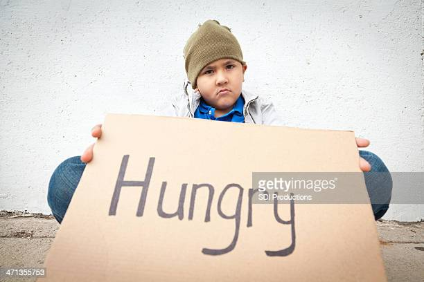 Sad homeless young boy holding a ''Hungry'' sign