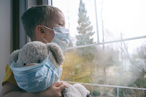 Sad illness child on home quarantine. Boy and his teddy bear both in protective medical masks sits on windowsill and looks out window. Virus protection, coronavirus pandemic, prevention epidemic. 1211982838