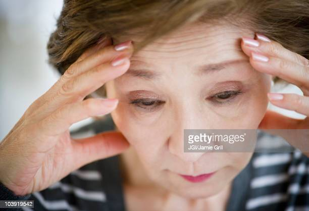 Sad Japanese woman with head in hands