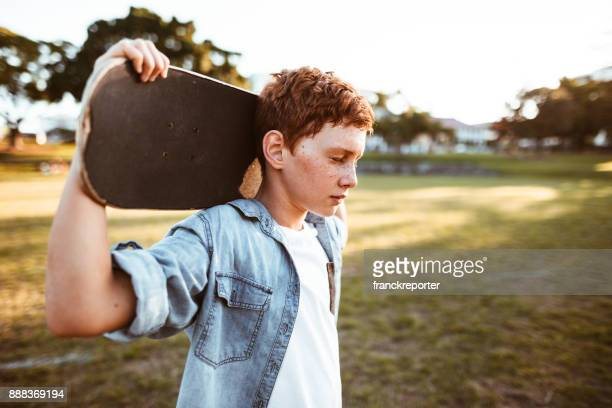 sad kid with the skateboard on the shoulder