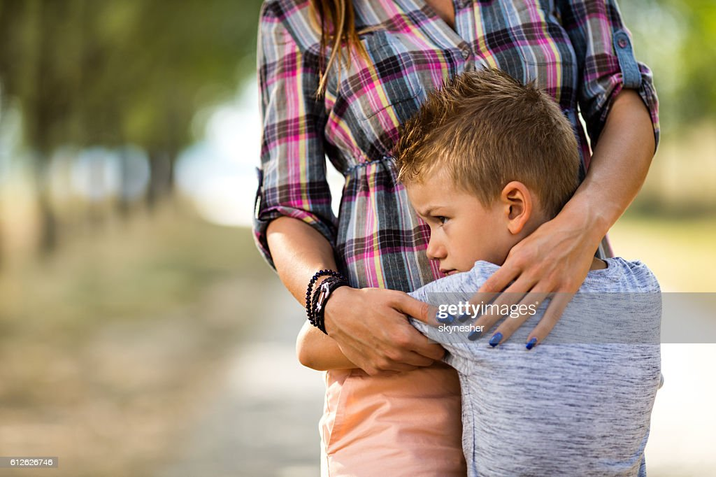 Sad little boy embracing his unrecognizable mother in nature. : Stock-Foto