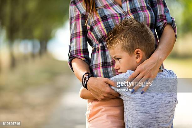 Sad little boy embracing his unrecognizable mother in nature.
