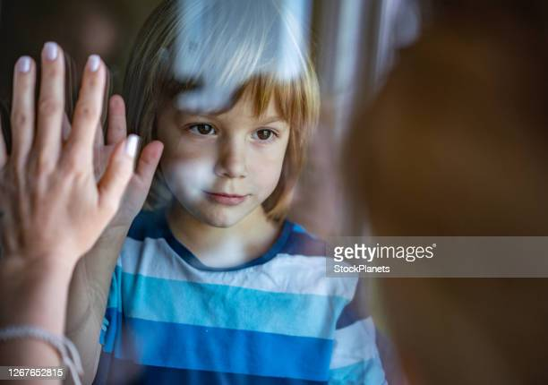 sad little boy in home during epidemic coronavirus - separation stock pictures, royalty-free photos & images